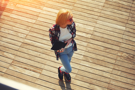 Top view shot of a young student girl standing with her digital tablet outdoors at sunny day, caucasian college student holding tablet while standing at campus looking away, flare sun light