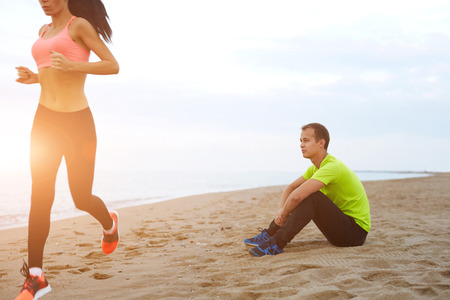 footsie: Young woman with beautiful figure running along the beach, couple working out against the sea at evening time, athletic man taking a break while his girlfriend exercising
