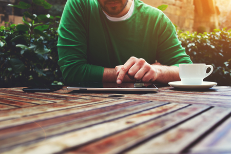 message: Cropped image young man sitting at the table with cup of coffee, digital tablet and smart phone, mans hands texting message on touch screen tablet while sitting on balcony terrace, flare sun