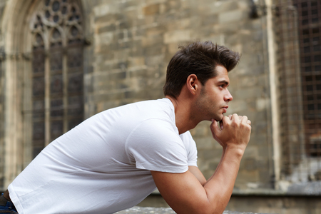 area sexy: Side shot portrait of handsome man resting chin on clasped hands, confident man thinking about his choice, pensive man standing against gothic building