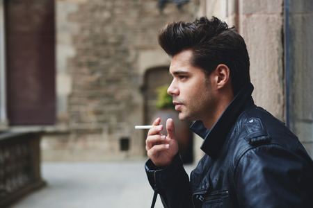 fag: Side shot view of fashionable young man smoking the cigarette while looking into the distance, handsome male model holding cigarette in the hand looking pensive and serious Stock Photo