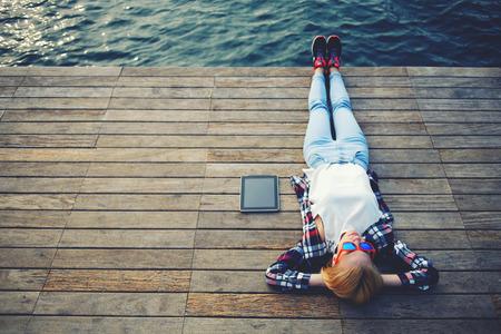 Vista superior de la mujer joven tendido en un embarcadero de madera disfrutando del sol, muchacha turística en vasos brillante que miente en el embarcadero de río, foto de la vendimia de la mujer joven se relaja en la naturaleza con la tableta, proceso cruzado Foto de archivo