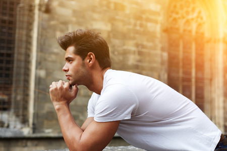 Side shot portrait of handsome man resting chin on clasped hands, confident man thinking about his choice, pensive man standing against gothic building, flare sun light, filtered image