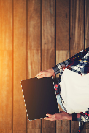 fem: Top view shot of a woman holding digital tablet with a blank screen- closeup, fem a hands holding blank digital tablet against beautiful wooden copy space area, flare sun light, filtered image Stock Photo