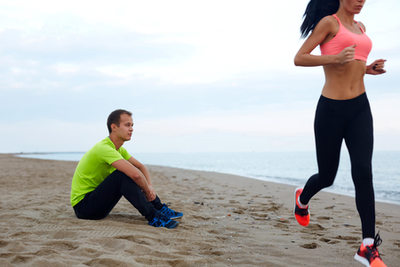 footsie: People working out on the beach, seated male runner relax after training and observe how his girlfriend engage the sport outdoors, couple having sports time next to the sea