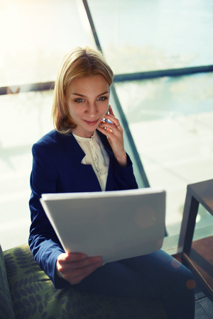 moneymaker: Portrait of young businesswoman having cell phone conversation while examining paperwork in light office interior sitting next to the window, filtered image, soft focus