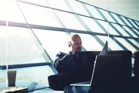 revisando documentos: Disparo de un apuesto hombre de negocios hablando por un teléfono móvil durante la revisión de los documentos que se sientan en el interior de la oficina moderna luz, hombre de negocios usando la computadora portátil durante la hora del café, la flama de la luz