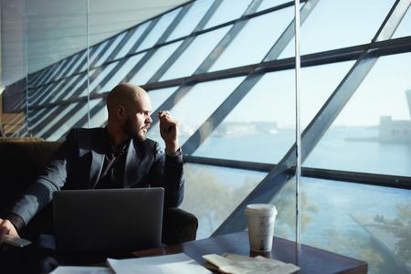 空港ホール ウィンドウ、深い思考の外を見て魅力的な若手実業家作業計画を考えて窓の外眺めてしんみりとハンサムの成功したビジネスマンのサイ