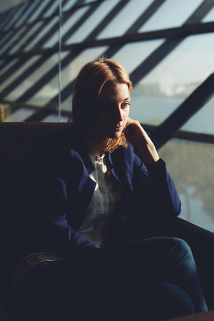 moneymaker: Portrait of pensive blonde hair woman sitting in airport hall next to the window, soft focus, filtered image