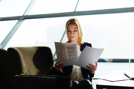 moneymaker: Portrait of attractive businesswoman reading papers or documents sitting in luxury coffee shop next to the window, soft focus, filtered image