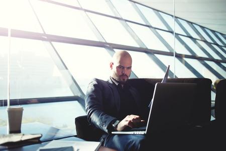 revisando documentos: Disparo de un empresario a escribir en el teclado del ordenador guapo y revisión de documentos sentado en la oficina moderna, entre la luz, el director general de examinar el papeleo en la cafetería, llamarada luz del sol Foto de archivo