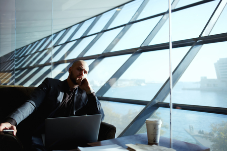 side shot: Side shot of handsome successful businessman pensively sitting near the window thinking about the work plan, attractive young business man relaxing in airport hall next to the window, deep in thought Stock Photo