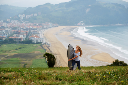 Blonde hair caucasian girl walking on mountain hill holding her surfboard in the cover, just arrived to the surf camp young woman inspect the surf spot, vacation holidays in nature Stock Photo