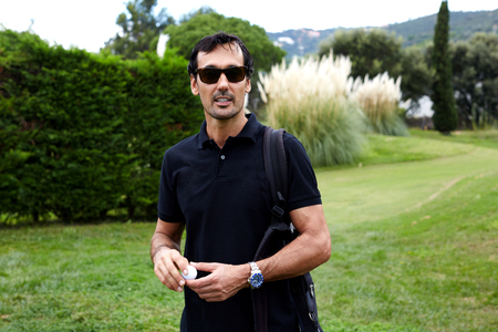 leisure time: Portrait of handsome rich man in glasses having good leisure time during golf game, golfer holding ball in the hands standing on beautiful green course Stock Photo
