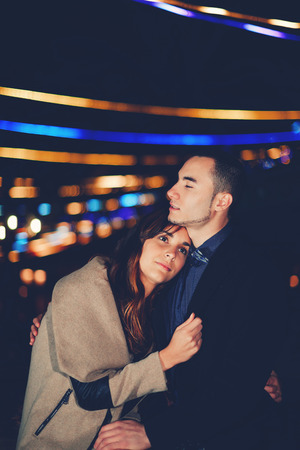 tender sentiment: Portrait of beautiful romantic couple embracing at outdoor night event with beautiful lights on background Stock Photo