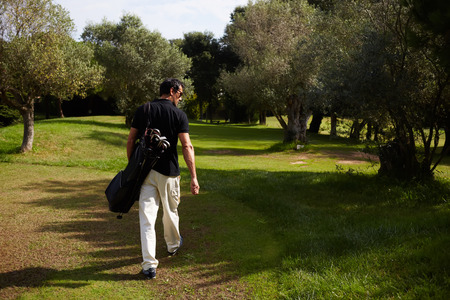 rich life: Rear view of professional male golfer walking to the next hole in golf course, good golf game at sunny summer day on the course