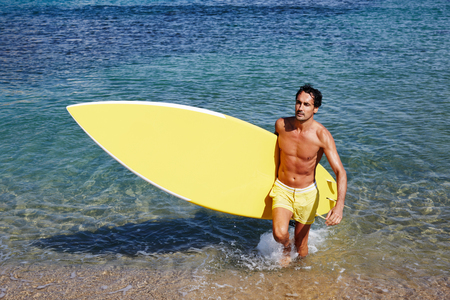 healthy men: Half length portrait of mature man with sexy abdominal coming out from the sea holding big copy space surfing board, handsome man standing on shoreline at beautiful sunny day