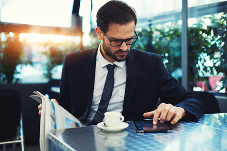 informed: Handsome young businessman use digital tablet pressing the button and locked to the screen, business man reading news during his breakfast