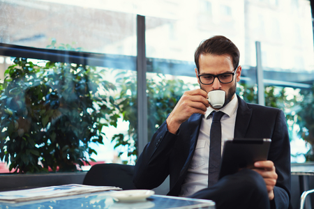 moneymaker: Attractive and smart business man using his tablet while having breakfast at coffee shop, businessman holding cup of coffee while read news on tablet Stock Photo
