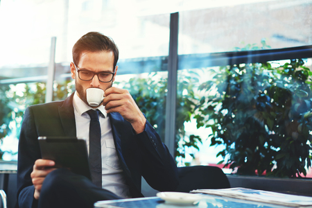 business table: Portrait of handsome successful man drink coffee and look to the digital tablet screen sitting in coffee shop, business man having breakfast sitting on beautiful terrace with plants Stock Photo