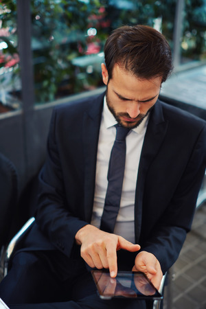moneymaker: Portrait of young businessman touching digital tablet screen sitting in coffee shop, attractive smart man use tablet pc browsing in internet