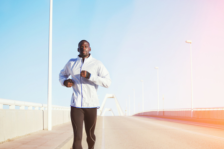 dark skinned: Half length portrait of a fit and athletic man running on a bridge road promenade outside - copy space area, dark skinned runner jogging against bright sky background, flare light with cross process