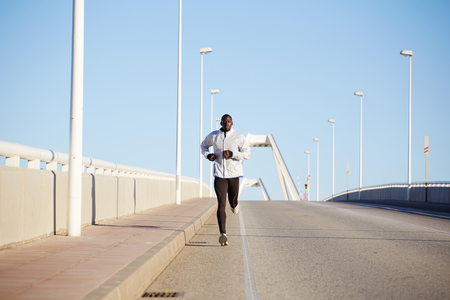 Full length shot of young sportive  runner training on the road against blue sky background Stock Photo