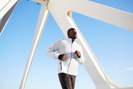 dark skinned: Low angle shot of an attractive dark skinned sporty man on a morning run outdoors over blue sky background