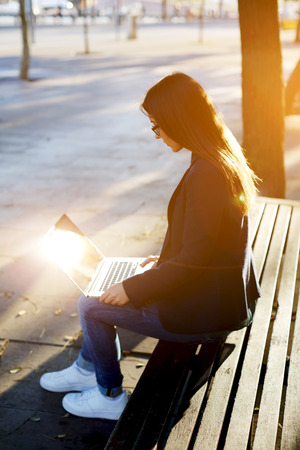 cross process: Young casual happy woman typing text on laptop while sitting on wooden bench, hipster girl using laptop outdoors, cross process image