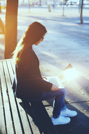 cross process: Attractive young woman using laptop outside, young student girl sitting on wood bench using laptop computer, cross process image