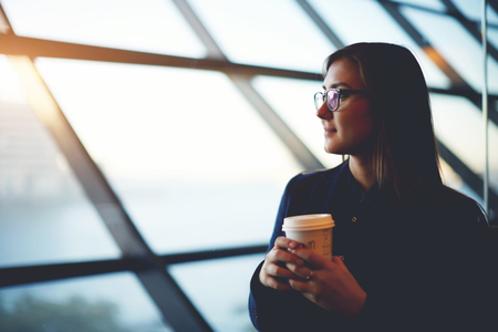 observers: Portrait of beautiful cute girl sitting near big window with coffee take away in airport Stock Photo