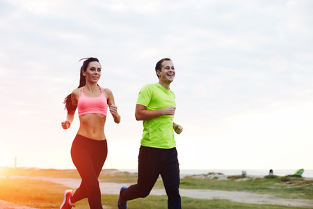 active wear: Full length portrait of young smiling couple running along the beach, athletic attractive people jogging in active wear enjoying perfect evening outdoors