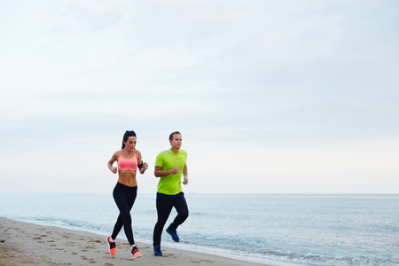 active wear: Full length portrait of young couple running along the beach, athletic attractive people jogging in active wear enjoying perfect evening outdoors