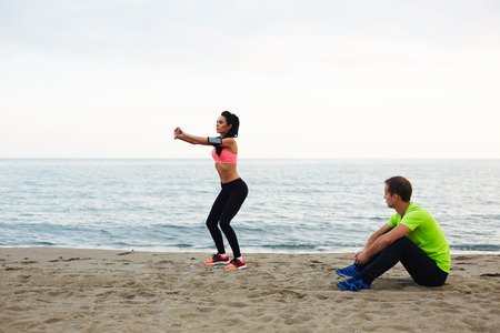 footsie: Personal trainer observing how young woman doing squat exercises, fitness couple training on the beach against sea at evening time