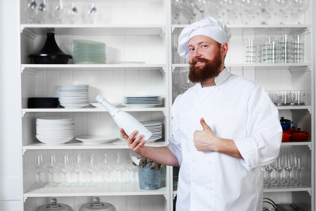 haute cuisine: Professional chef of luxury haute cuisine in white uniform and hat holding bottle of champagne and showing sign super