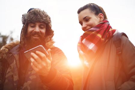 adentro y afuera: Hermosa pareja de excursionistas que ríe mientras mira a la pantalla del móvil, joven pareja de mochileros disfrutando de un día en la naturaleza en conjunto