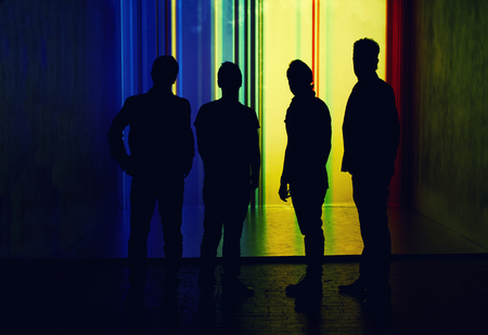 team spirit: Silhouette of four people standing on highlighted wall background, team spirit concept