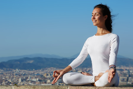 yoga meditation: Yoga on high altitude with big city on background, smiling woman seated in yoga pose on amazing city background, woman meditating yoga and enjoying sunny evening, woman makes yoga on mountain hill