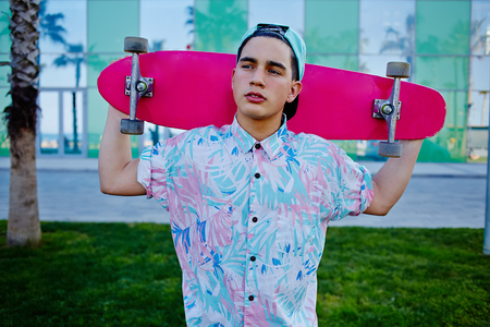 prank: Young stylish man in bright summer clothes standing with pink long-board on beautiful glass background with reflected palm trees, cool teenager holding his long board looking away prank