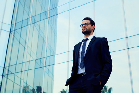 moneymaker: Confident business man in glasses standing against office building with hands in the pockets