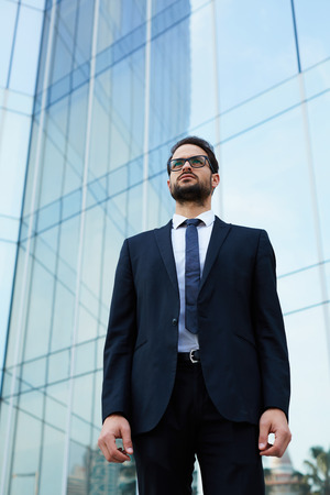 moneymaker: Half length portrait of serious handsome businessman at office building Stock Photo