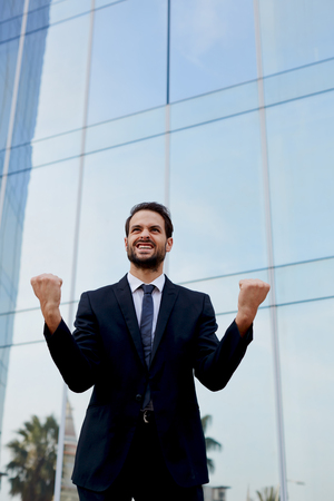 moneymaker: An excited man with winner spirit celebrating success, happy businessman with his arms raised standing near office building, overjoyed businessman raising his arms in victory outside a office building