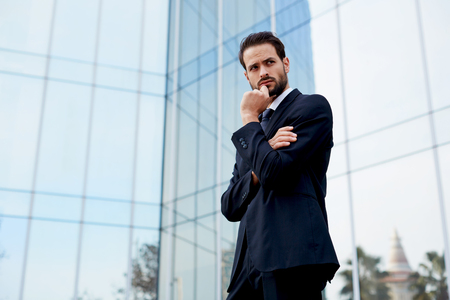 moneymaker: Pensive businessman standing with arm crossed and hand against his mouth looking away