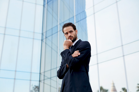 moneymaker: Portrait of serious pensive business man standing with arm crossed and hand against his mouth Stock Photo