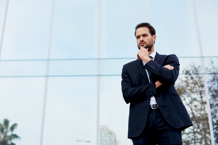 moneymaker: Half length portrait of pensive young businessman standing against office building