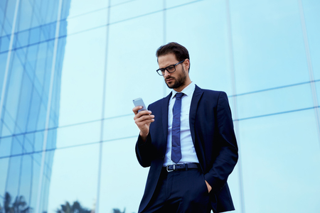 moneymaker: Confident businessman standing outside using a cellphone, filtered image, businessman using technology Stock Photo