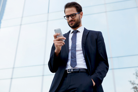 moneymaker: Portrait of handsome businessman looking at cell phone standing near office