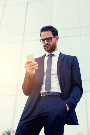 insider information: Half length portrait of handsome businessman reading text message on his smartphone Stock Photo