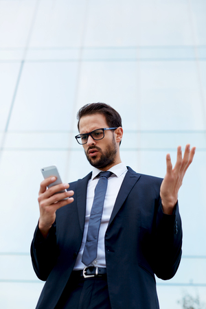 insider information: Handsome businessman receiving shocking news as he reads a text message on mobile phone Stock Photo