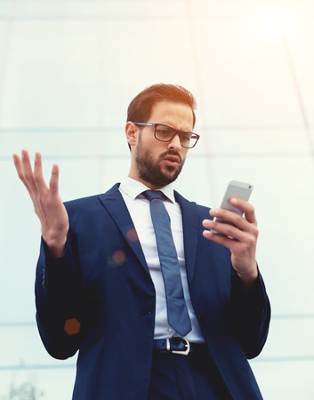 insider information: Handsome unhappy, surprised and shocked executive looking at smart phone receiving bad news, negative human emotions, facial expression, reaction
